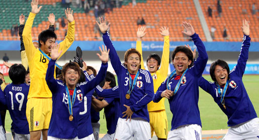 Japanese players celebrate after winning gold medal in Asian Games football final against the UAE. —AFP Photo